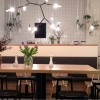 The cafe features lots of light timber tables, with black chairs and interesting lighting